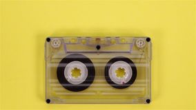 Retro music compact cassette reeling tape on yellow. Background - closeup stock footage
