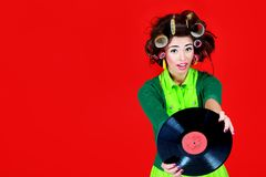 Retro music lover. Portrait of a woman with curlers on her hair holding gramophone record. Retro style Royalty Free Stock Images