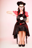 Retro music. Pinup girl with vinyl record. Retro. Full length of stylish pinup woman girl in eyeglasses pointing at old vinyl record on pink stock images