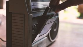 Retro music player. Man put a cassette tape into retro music play, vintage style stock video