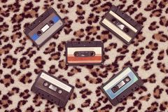 Retro music 1980s authentic composition. With audio cassettes on leopad background stock image