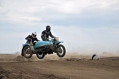 Retro MX ruiter door motorfiets met sidecar Ural stock foto