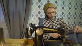 Retro naaistersmeisje naait doek met oude handhand naaimachine De vrouwenwerken thuis of workshop bij nacht met stock videobeelden