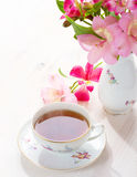 Retro natura morta con la tazza di tè e dei fiori Immagini Stock