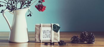 Retro, natural and simple xmas home decoration with beautiful window light. Wrapped Christmas Present. On a table Royalty Free Stock Photos