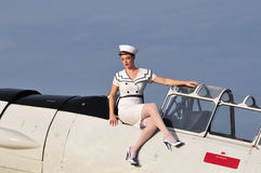 Retro navy girl with a vintage aircraft Royalty Free Stock Photography