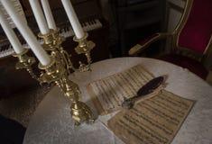 Retro notblad och fjädern av den tid och en härlig guld- ljusstake royaltyfria bilder