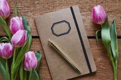 Retro notebook surrounded by pink tulips. In spring atmosphere valentines day poem royalty free stock photography