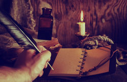 Retro objects feather and leaher book with candle light Royalty Free Stock Photography