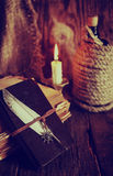 Retro objects feather and leaher book with candle light Stock Images