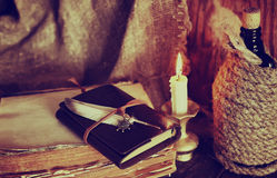 Retro objects feather and leaher book with candle light Royalty Free Stock Image