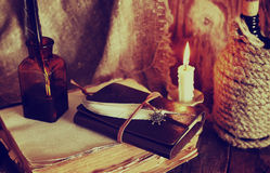Retro objects feather and leaher book with candle light Stock Photos