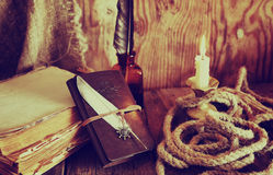 Retro objects feather and leaher book with candle light Stock Photography