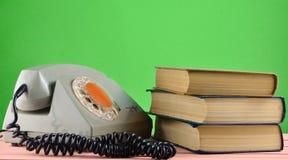 Retro obrotowy telefon, sterta książki na biurku odizolowywał agains Obraz Royalty Free