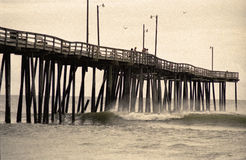 Retro Ocean Pier. Large fishing pier with rough ocean surf. Vintage image with noise & sepia tone added Royalty Free Stock Photo