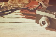 Retro old camera with black leather case and velvet vintage photo on white wooden background copy space. royalty free stock images