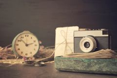 Retro old camera with pile of photos, letters, malachite box and antique watches on wooden background. Memories, nostalgia,. Love, romance, concept. Selective stock photo