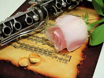 Retro old clarinet. Wedding picture with a clarinet and a rose on the background of notes royalty free stock photography
