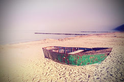 Retro old film effect on rusty steel boat on the beach Stock Image