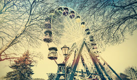 Retro old film faded picture of ferris wheel in a park. Stock Images