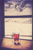 Retro old film style glass of hot tea on wooden table. Royalty Free Stock Images