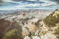 Retro old film stylized legs with worn out hiking shoes. Stock Images