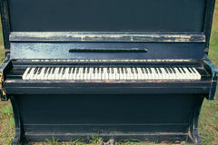Retro old piano with shabby and cracks on the grass, music. And vintage concept Royalty Free Stock Photography