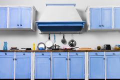 Retro old vintage pin up blue interior kitchen. For cooking with kitchen extract and cooking tools: colander, frying pan, toaster, tray and pink sweet cupcakes royalty free stock photos