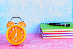 Retro orange alarm clock on table with note book and pen Royalty Free Stock Image