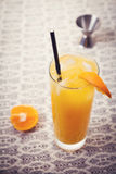 Retro orange cocktail drink on lace tablecloth Stock Image
