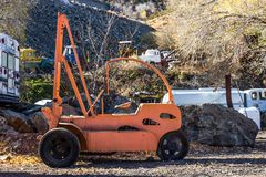 Retro Orange Fork Lift In Salvage Yard. Retro Orange Fork Lift With Three Wheels In Salvage Yard Stock Images