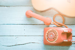 Retro orange-red telephone and the guitar Stock Photo