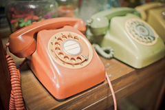 Retro orange and Telephone on wooden table Stock Photography
