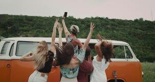 Retro oranje bestelwagen, in het midden van gebiedsgroep vrienden, die aardige video nemen of selfies van telefoon, gelukkig zij stock videobeelden