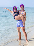 Retro pair on the sea bech. Man in swimsuit holding in his arms a women in a swimsuit on the sea beach Royalty Free Stock Photo