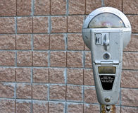 Retro parking meter with brick background Royalty Free Stock Photo