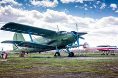 Retro passenger biplane and small sports airplane at the ground airfield stock image