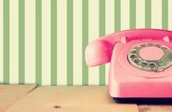 Retro pastelowe menchie telefonują na drewnianym stole i abstrakcjonistycznym retro geometrycznym pastelu wzoru tle retro filtruj Obrazy Stock