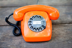 Retro phone orange color, handset receiver on wooden textured background. Shallow depth field photography. Royalty Free Stock Photo