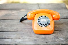 Retro phone orange color, handset receiver on wooden textured background. Shallow depth field photography. Retro phone orange color, handset receiver on wooden Stock Image