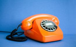 Retro phone orange color, vintage handset receiver on blue background. Shallow depth field photography. Royalty Free Stock Photos
