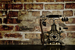 Retro Phone - Vintage Telephone on Old Desk. With Brick Wall Stock Photo