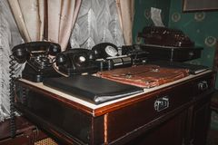Retro phones, vintage cash register, old printing machine, folders and briefcase. On the table Royalty Free Stock Photos