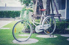 Retro photo of beautiful artificial flowers in bicycle at garden Royalty Free Stock Photography