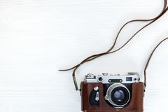 Retro photo camera in brown leather case on white wooden desk. Vintage photo camera in brown leather case on white wooden background Stock Image