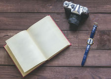 Retro photo camera, watch and open book on the wooden table Royalty Free Stock Photo