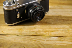 Retro photo camera on a wooden background Royalty Free Stock Photos