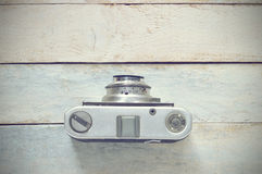 Retro photo camera on a wooden background, top view. Stock Photo
