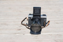 Retro photo camera. On wooden surface Royalty Free Stock Images