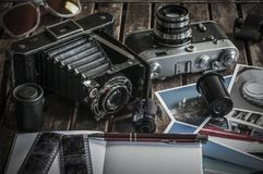 Retro photo cameras on a table. Old retro cameras on a table with photographs, negatives and films with Copy Space royalty free stock images